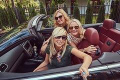 3 счастливых модных женских друз принимают фото selfie в роскошном автомобиле cabriolet, во время их каникул отключения Стоковое Изображение
