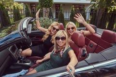 3 счастливых модных женских друз принимают фото selfie в роскошном автомобиле cabriolet, во время их каникул отключения Стоковые Изображения RF