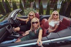 3 счастливых модных женских друз принимают фото selfie в роскошном автомобиле cabriolet, во время их каникул отключения Стоковое Изображение RF