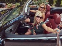 3 счастливых модных женских друз принимают фото selfie в роскошном автомобиле cabriolet, во время их каникул отключения Стоковые Фото
