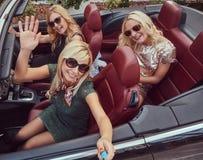 3 счастливых модных женских друз принимают фото selfie в роскошном автомобиле cabriolet, во время их каникул отключения Стоковое фото RF