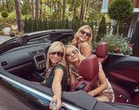 3 счастливых модных женских друз принимают фото selfie в роскошном автомобиле cabriolet, во время их каникул отключения Стоковая Фотография RF