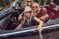 3 счастливых модных женских друз принимают фото selfie в роскошном автомобиле cabriolet, во время их каникул отключения Стоковое Фото