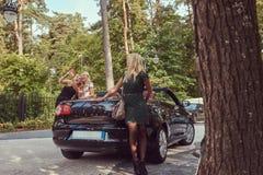 3 счастливых модных женских друз стоя близко роскошный автомобиль cabriolet в парке Стоковое фото RF
