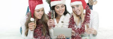 3 счастливых молодой женщины в костюмах Санта Клауса смотря таблетку Стоковое Фото
