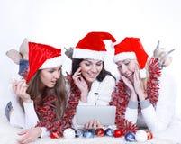 3 счастливых молодой женщины в костюмах Санта Клауса смотря t Стоковая Фотография RF
