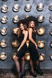 2 счастливых молодой женщины в черных костюмах хеллоуина ведьмы на партии Стоковые Фотографии RF