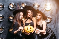 2 счастливых молодой женщины в черных костюмах хеллоуина ведьмы на партии Стоковое Фото