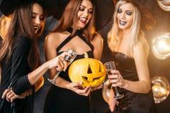2 счастливых молодой женщины в черных костюмах хеллоуина ведьмы на партии Стоковое Изображение