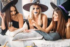 2 счастливых молодой женщины в черных костюмах хеллоуина ведьмы на партии Стоковое фото RF