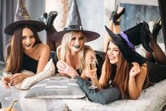 2 счастливых молодой женщины в черных костюмах хеллоуина ведьмы на партии Стоковые Изображения