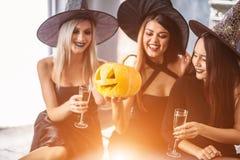 2 счастливых молодой женщины в черных костюмах хеллоуина ведьмы на партии Стоковая Фотография