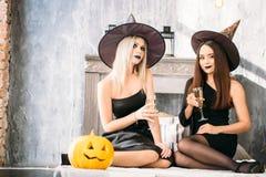 2 счастливых молодой женщины в черных костюмах хеллоуина ведьмы на партии сидя на кровати Стоковая Фотография