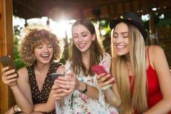 3 счастливых молодой женщины имея потеху с умным телефоном стоковые фотографии rf