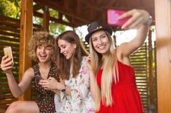 3 счастливых молодой женщины имея потеху с умным телефоном стоковые фото