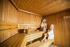 2 счастливых молодой женщины ослабляя в сауне Стоковые Фотографии RF