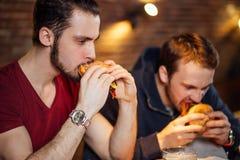 2 счастливых мужских друз есть вкусные бургеры в баре Стоковые Изображения