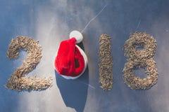 2018 счастливых номеров Нового Года с шляпой риса и красного цвета Санта Клауса Стоковое фото RF