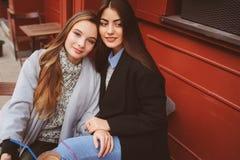 2 счастливых подруги говоря и выпивая кофе в городе осени в кафе Встреча хороших друзей, молодых модных студентов Стоковые Фото