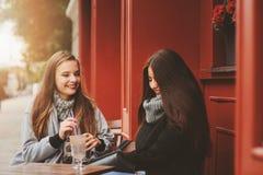 2 счастливых подруги говоря и выпивая кофе в городе осени в кафе Встреча хороших друзей, молодых модных студентов Стоковые Фотографии RF