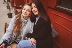 2 счастливых подруги говоря и выпивая кофе в городе осени в кафе Стоковые Фотографии RF