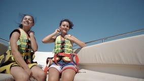 2 счастливых предназначенных для подростков девушки нося ремни безопасности на шлюпке Стоковое фото RF