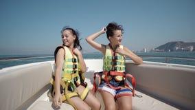 2 счастливых предназначенных для подростков девушки нося ремни безопасности и сидя на яхте Стоковая Фотография