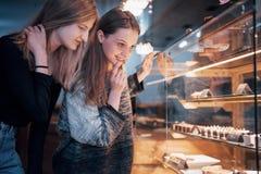 2 счастливых привлекательных девушки выбирая очень вкусные ganaches, пралине и шоколады Стоковые Изображения