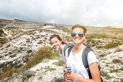 2 счастливых привлекательных маленькой девочки путешествуя совместно, пеший туризм, nat Стоковое Изображение
