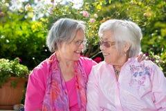 2 счастливых старших женщины беседуя в саде Стоковое Изображение RF