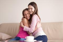 2 счастливых усмехаясь молодых подруги давая одину другого большое объятие Стоковые Фотографии RF