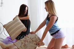 2 счастливых усмехаясь подруги имеют бой подушек Стоковые Фото