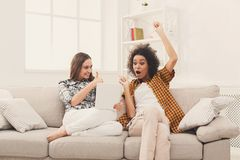 2 счастливых excited женских друз используя таблетку Стоковые Фотографии RF