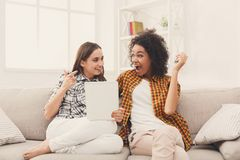 2 счастливых excited женских друз используя таблетку Стоковое Изображение RF
