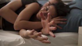 счастлив к совместно Радостный молодой мужчина и женский лежать в кровати покрытой с белыми листами, усмехающся, тратящ славное в сток-видео