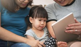 Счастье азиатской семьи сидя и играя цифровая таблетка Стоковые Изображения RF