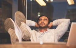 Счастье бизнесмена ослабляя на его рабочем месте Стоковые Изображения RF