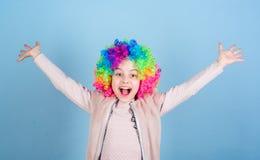 Счастье живет жизнь изнутри Счастливый ребенок маленькой девочки нося яркие волосы парика усмехаясь со счастьем стоковое изображение rf