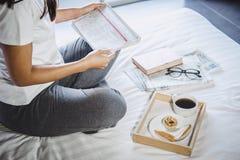 Счастье молодой женщины на спальне в наслаждаться книгами чтения и n Стоковая Фотография
