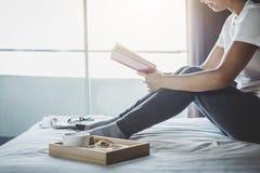 Счастье молодой женщины на спальне в наслаждаться книгами чтения и n Стоковое Фото