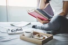 Счастье молодой женщины на спальне в наслаждаться книгами чтения и n Стоковое Изображение