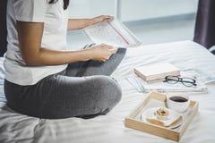 Счастье молодой женщины на спальне в наслаждаться книгами чтения и n Стоковое Изображение RF