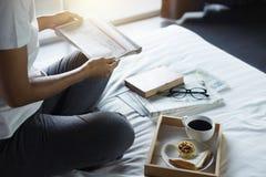 Счастье молодой женщины на спальне в наслаждаться книгами чтения и n Стоковые Фото