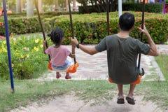 Счастье семьи на празднике, отец и дочь сидят и отбрасывают в парке стоковые фотографии rf