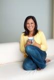 Счастливая азиатская женщина наслаждаясь чашкой кофе Стоковое фото RF