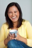 Счастливая азиатская женщина наслаждаясь чашкой кофе Стоковое Изображение