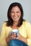 Счастливая азиатская женщина наслаждаясь чашкой кофе Стоковое Изображение RF