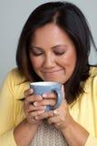 Счастливая азиатская женщина наслаждаясь чашкой кофе Стоковые Фото