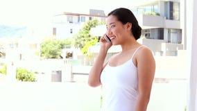 Счастливая азиатская женщина отправляя СМС на ее телефоне видеоматериал