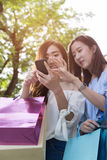 счастливая азиатская женщина с smartphone и красочными хозяйственными сумками на Стоковая Фотография RF